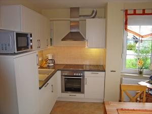 Voll ausgestattete Küche mit Mikrowelle, Backofen, Cerankochfeld und Geschirrspüler
